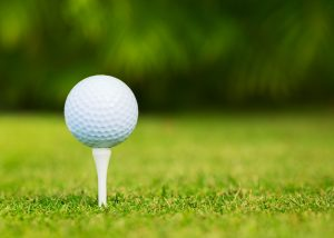 23467329 - close up view of golf ball on tee on golf course